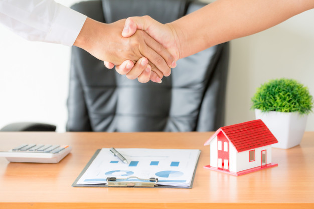 agent-and client shaking hands after signed contract